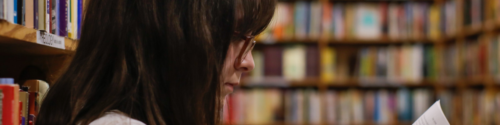 Young woman reading book in library stacks, image by Eliott Reyna